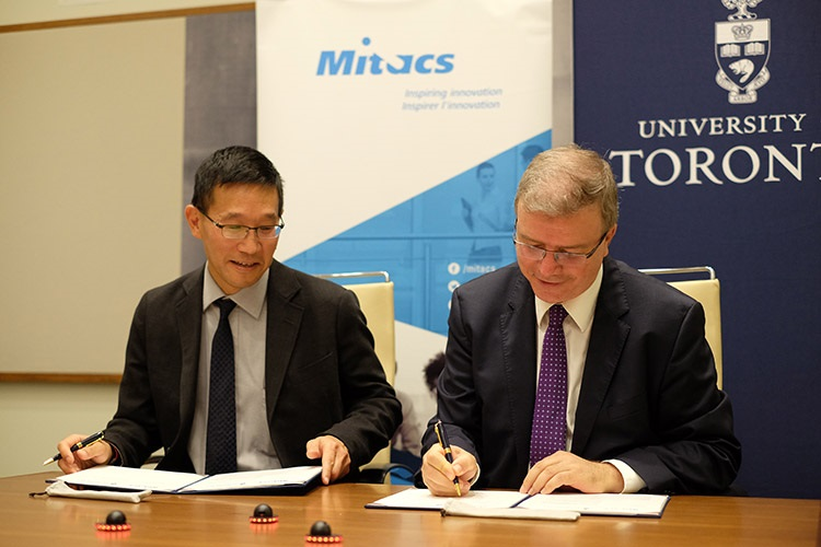 Christopher Yip, U of T's associate vice-president of international partnerships, signs the funding agreement with Ridha Ben Mrad, Mitacs' chief research officer and associate academic director. Photo by Geoffrey Vendeville.