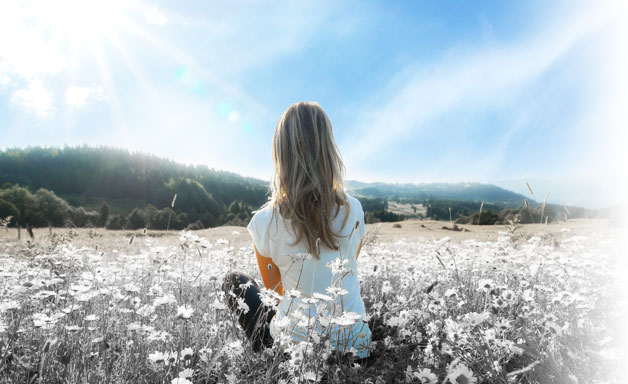 Girl sitting in the fields looking at the blue sky