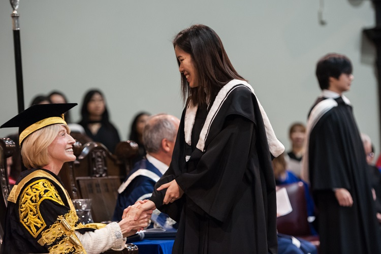 Chancellor Rose Patten shakes hands with a graduate in U of T's Convocation Hall in November, 2018. Photo by Lisa Sakulensky.