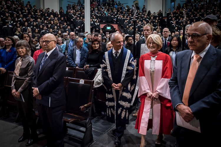 Rose Patten enters Convocation Hall with U of T President Meric Gertler in advance of the robing ceremony. Her husband Tom Di Giacomo is second from the left. Photo by Lisa Sakulensky.
