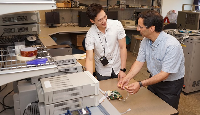 Professor Ali Sheikholeslami demonstrates the features of a test chip designed by his former PhD student Joshua Liang to his MASc student, Danny Yoo, in the lab (photo by Jessica MacInnis)