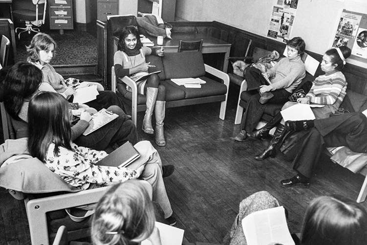 Ceta Ramkhalawansingh gestures as she talks to a circle of women sitting in chairs in 1975.