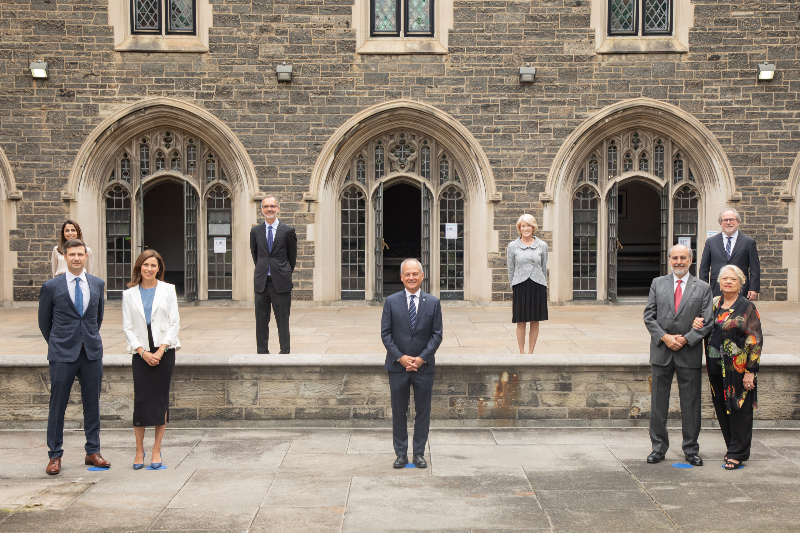 Standing at safe distances, standing in two rows outside of Hart House following the announcement of the Temerty Foundation's historic gift to U of T Medicine. Back row (left to right): Hira Raheel, MD Candidate; Trevor Young, Dean, Temerty Faculty of Medicine; Rose Patten, Chancellor, U of T; David Palmer, Vice-President, Advancement, U of T; front row: Mike Lord; Leah Temerty-Lord; Meric Gertler, President, U of T; James Temerty; Louise Temerty.