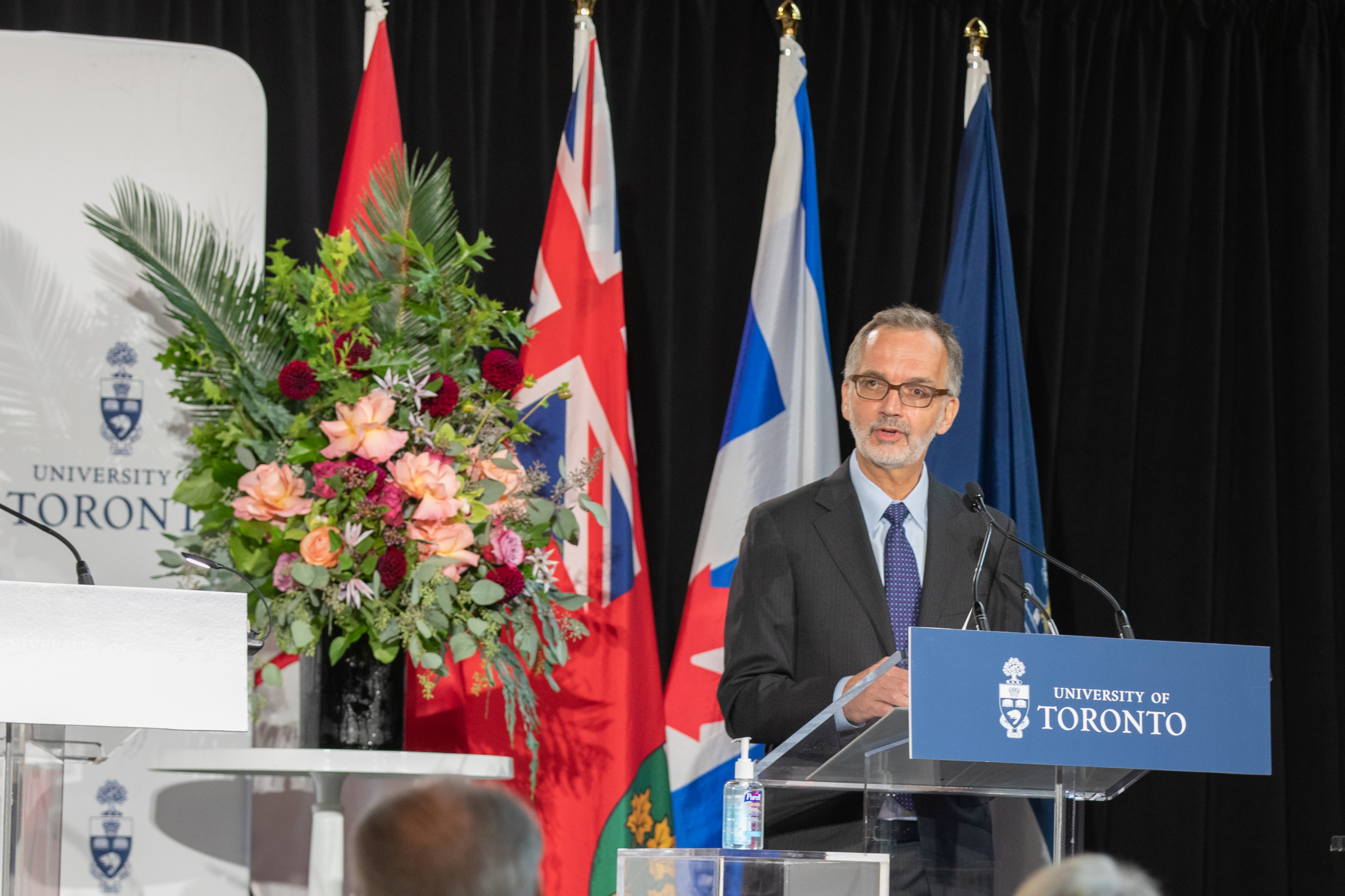 Dean of the Temerty Faculty of Medicine, Trevor Young, standing and speaking at the podium during the Temerty gift announcement event.