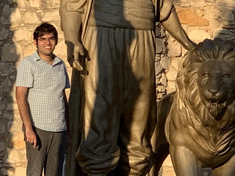 Arshan Hasan smiles as he stands next to an ancient statue of a giant petting a lion.