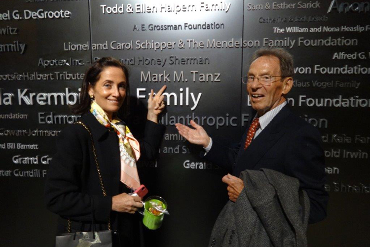 Jacqueline and Mark Tanz smile while pointing at Mark Tanz's name on a wall listing donors to the Tanz Centre.