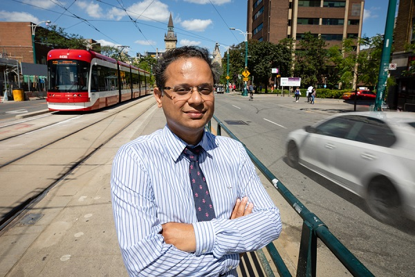 Khandker Nurul Habib smiles as he stands on a streetcar platform in the middle of busy Spadina Avenue.