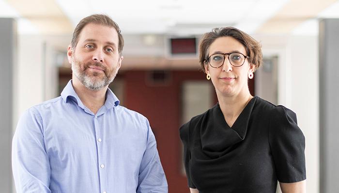 Robert Kozak and Samira Mubareka stand side by side in a hallway.
