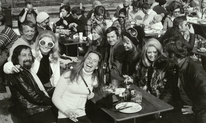 Linda Munk laughs, holding a cigarette and sitting at an outdoor restaurant table with many smiling people in 1970.