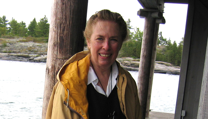 Linda Munk smiles, wearing a raincoat and standing on a roofed wooden dock before a rocky, wooded shoreline.