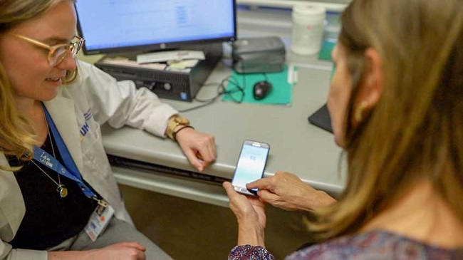 A doctor and a patient look at a smartphone screen together.