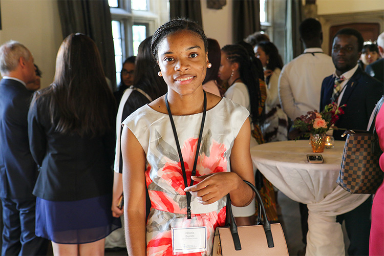 Nikiela Baptiste smiles while taking part in a social reception in a large hall.