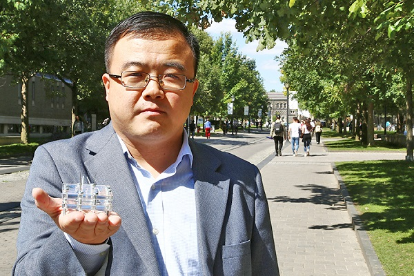 Xinyu Liu stands on King's College Road and holds up a small box made of metal and clear plastic.