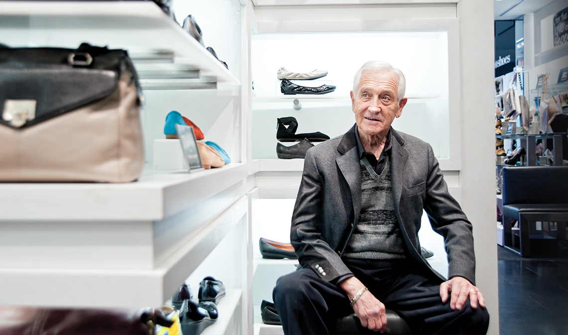 Leonard Simpson, seated in front of shelf with shoes.