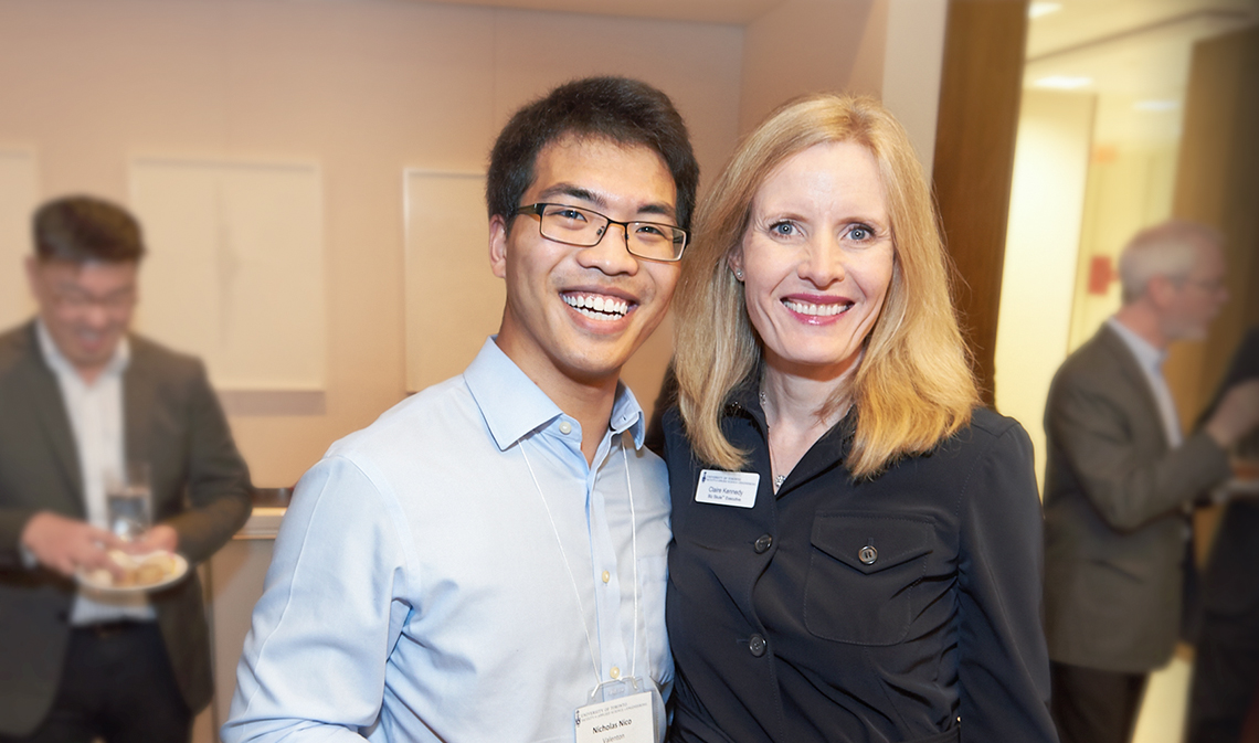 Claire Kennedy smiling with a student, at a reception indoors.