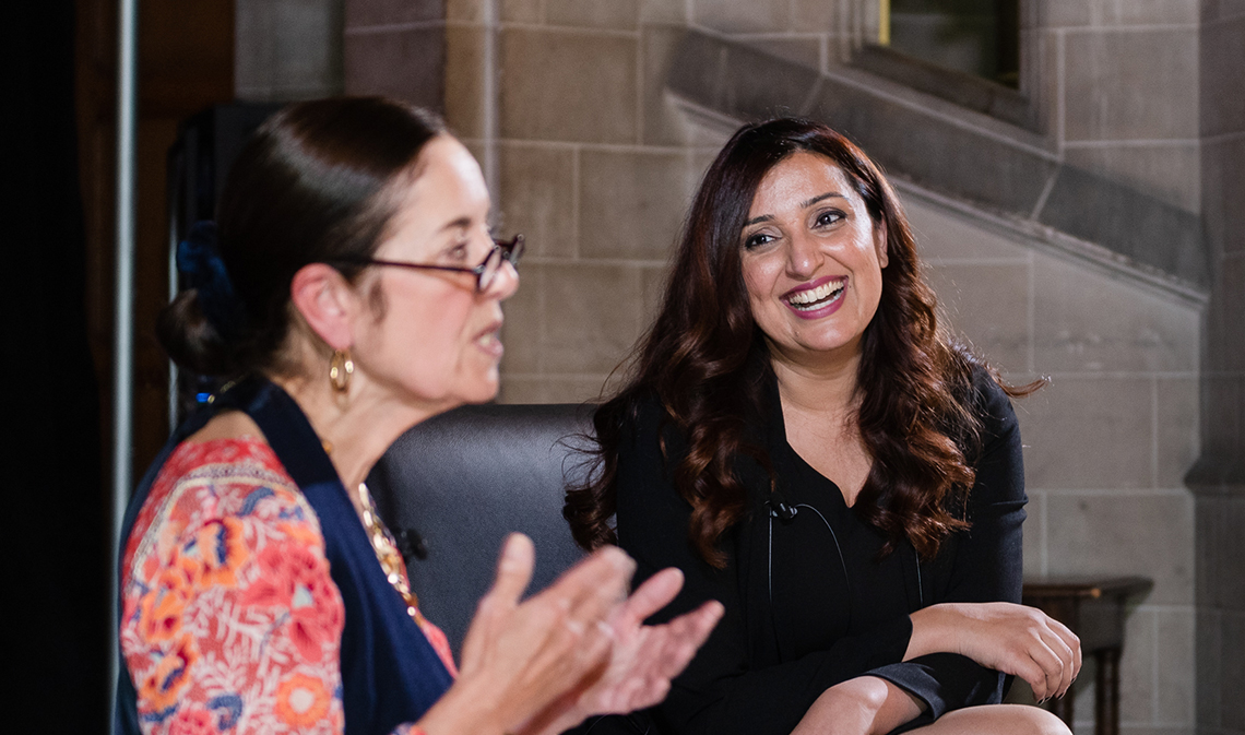 Samra Zafar, seated, smiles and looks on as Wendy M. Cecil speaks in a building interior.