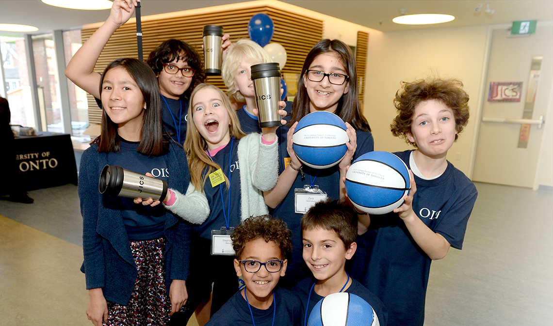 Elementary school students smiling and holding basketballs inside at the official opening of the Dr. Eric Jackman Institute of Child Study