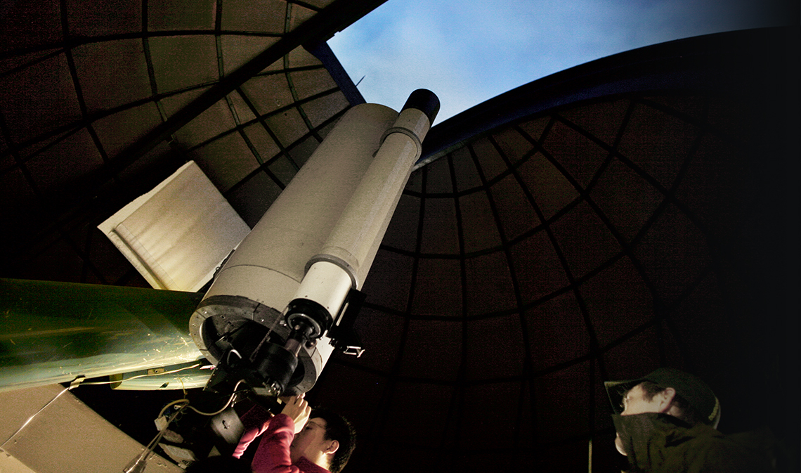 A person looking into a telescope through observatory ceiling.