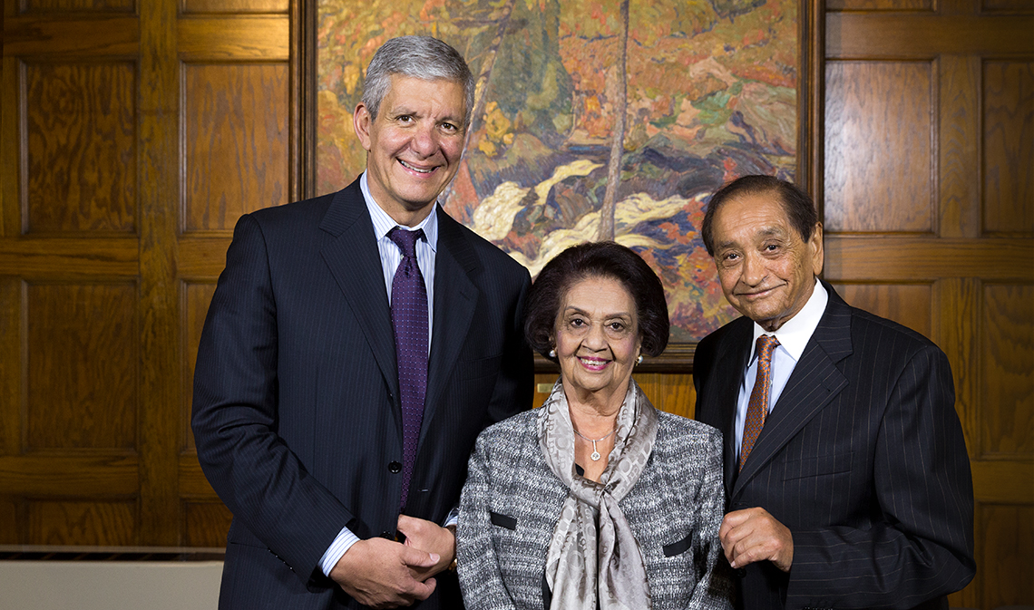 Sherif El-Defrawy, Gulshan Nanji and Pyarali Nanji standing and smiling in front of a wood panel wall with a painting in the background.