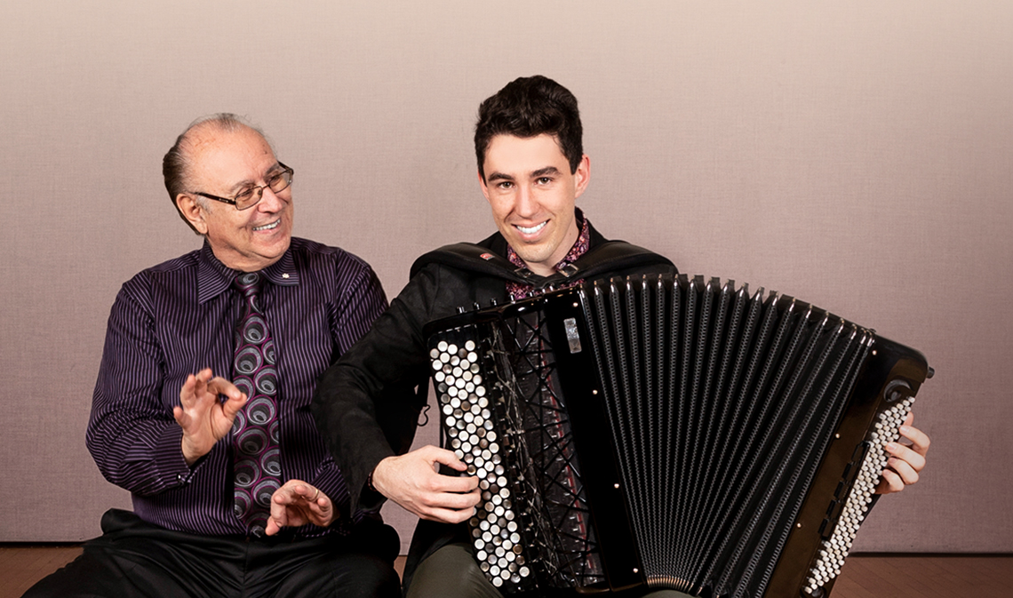 Joseph Macerollo (left) and Michael Bridge sitting and smiling, while Michael plays the accordion.