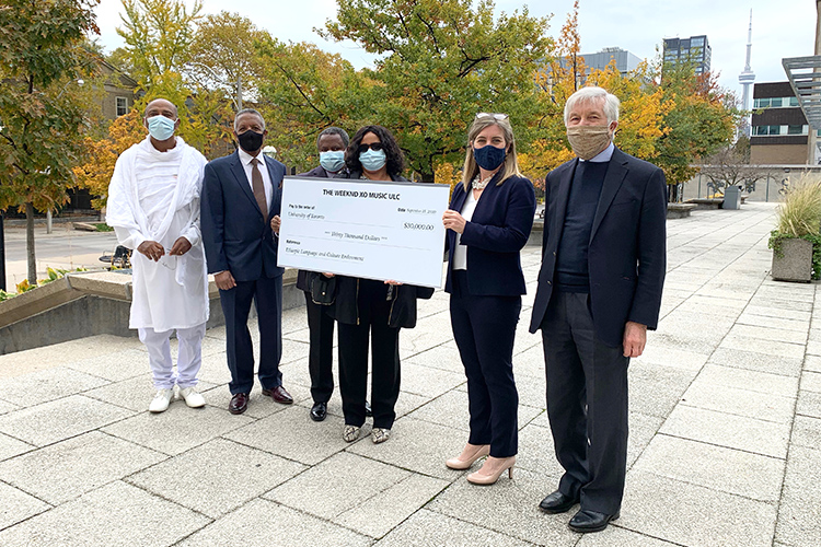 Two community representatives, The Weeknd's parents, and two U of T representatives stand with a large-sized cheque.