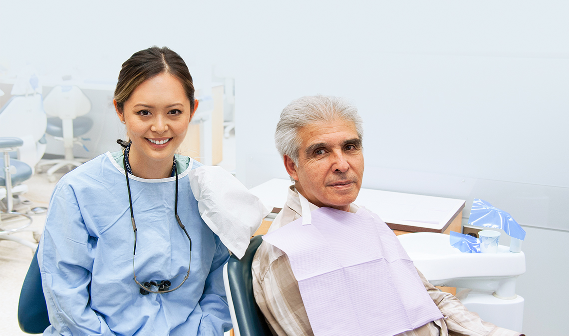 Dentistry student Carolyn Chuong, seated next to patient Oscar Rios.