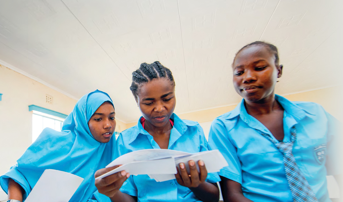 Three students looking at a piece of paper.