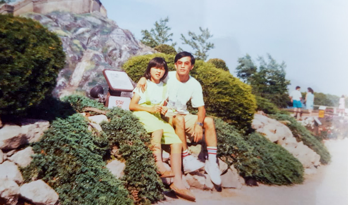 Vicky Nguyen (left) with her uncle Phu Hoang pictured in 1992, sitting outdoors on a sunny day.